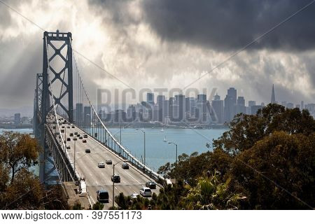 View of traffic on the Bay Bridge with downtown San Francisco and stormy sky in background