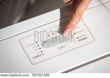 Woman Turning On Air Dryer, Purifier, Dehumidifier, Humidity Indicator, Air Ionizer Or Water Contain