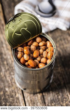 Mix of legume beans and chickpeas with sauce in can on wooden table.