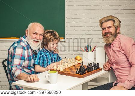 Father Teaching Son Play Chess. Grandfather Educated Grandson. Grandfather And Grandson Concept