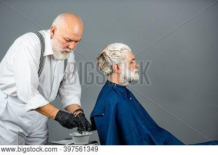 Senior Hairdresser Applying Dye To Man Hair. Process Of A Guy Having His Hair Dyed At Hairdresser. B