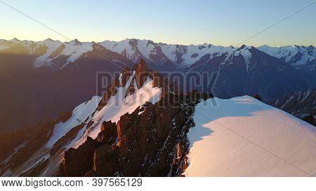 Epic Red Dawn On Top Of Snowy Mountains. Top View From A Drone. Huge Rocks Covered With Snow, The Le