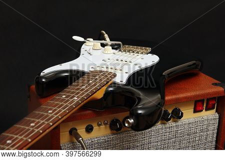 Brown Tube Combo For Guitar With Black Guitar On The Black Background.