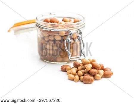 Mix of legume beans and chickpeas in sauce isolated on white background.