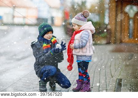 Toddler Girl And School Kid Boy In Colorful Winter Fashion Clothes Having Fun And Playing With Snow,
