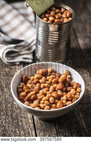 Mix of legume beans and chickpeas with sauce in bowl on wooden table.
