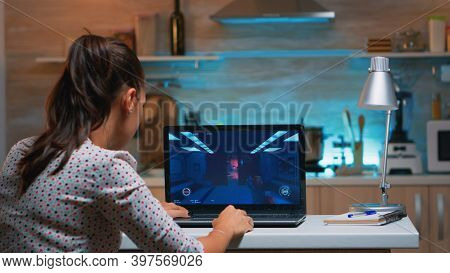 Woman Gamer Sitting At Home In Kitchen Testing New Game On Professional Laptop. Tired Player Gaming