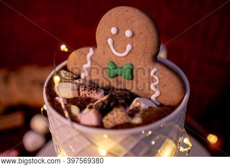 Delicious Cup Of Hot Chocolate With A Smiling Gingerbread Man's Cookie Dipped In Cinnamon Dusted Cho