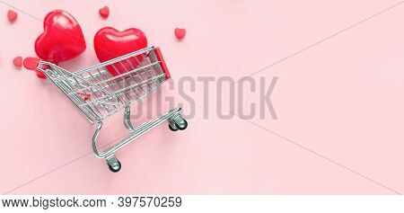 Valentine's Day Online Shopping. Shopping Cart With Hearts On A Pink Background. Seasonal Holiday Sa