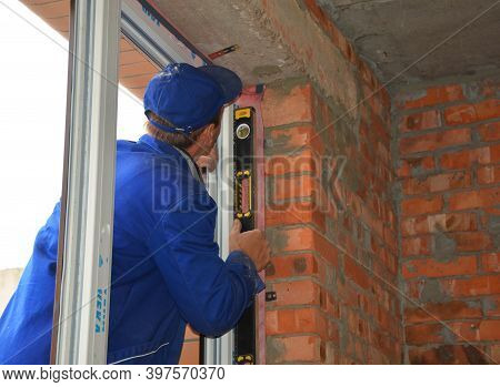 Kyiv, Ukraine - November 17, 2020: A Professional Upvc Window Installer Is Checking With A Spirit Le
