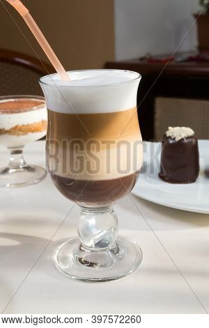 Hot Layered Coffee Served On A Table With Desserts