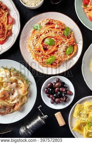 Italian Food, Shot From Above On A Black Background. Spaghetti With Basil, Olives, Wine Cork, Raviol
