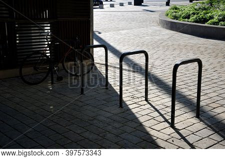 Five Wheel Stands Of Black Metal Bent Tube In The Shape Of A Rectangle In Front Of The Retaining Wal