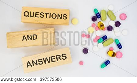 Questions And Answers Is On Long Wooden Blocks On A White Background With Pills. Medical Concept.