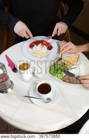 People Eating Breakfast In A Cafe With Coffee And Tea