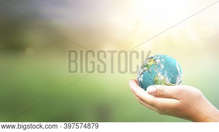 Hands Holding Earth Global In Lush Green Environment With Sunlight . Elements Of This Image Furnishe