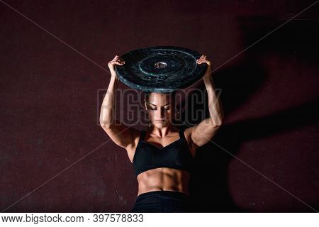 Young Strong Sweaty Fit Muscular Girl With Big Muscles Doing Sit Ups With Barbell Weight Plate For A