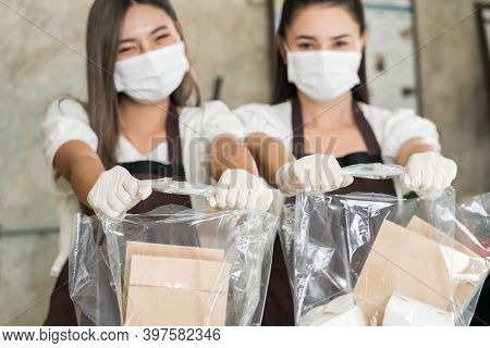 Close up waitress wear protective face mask smile and hold shopping bag for take away or takeout food. This essential service is very popular while city lockdown from coronavirus COVID-19 Pandemic