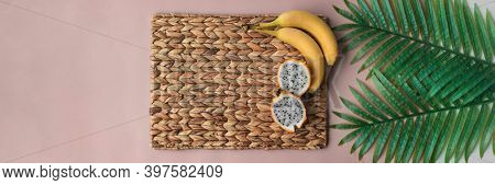 Pitaya and bananas tropical fruits top view of breakfast morning table background. Banner on pink and straw placemat.