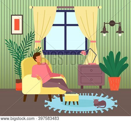 Man Sitting At Armchair In Living Room Near Window. Guy Enjoy Leisure Time, Like Spend Time At Home.