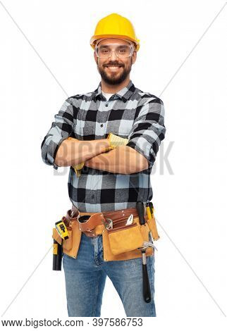 profession, construction and building - happy smiling male worker or builder in helmet and goggles with crossed arms over white background