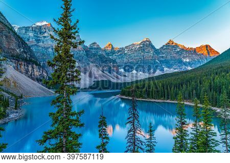 Moraine Lake Sunrise Time In Summer Sunny Day. Snow-covered Valley Of The Ten Peaks Turning Red And