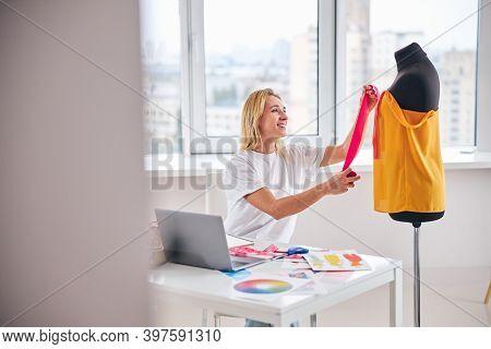 Joyous Fashion Designer Adding The Trim To A New Garment