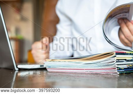 Manager Looks At Magazines And Laptop In The Office, Magazines Are In The Foreground