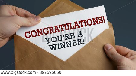 Male Hands Holding Craft Envelope With Text Congratulations You're A Winner On Blue Background, Comm