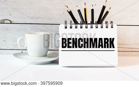 The Word Benchmark Is Written In A White Notepad Near A White Cup Of Coffee On A Light Background