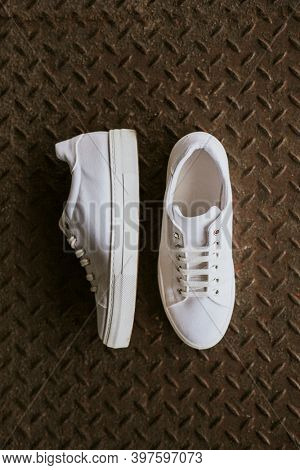 White canvas sneakers on metal texture