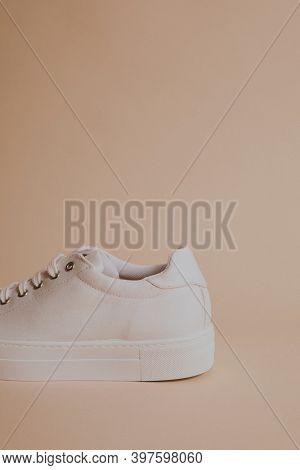 Woman's white canvas sneaker on beige