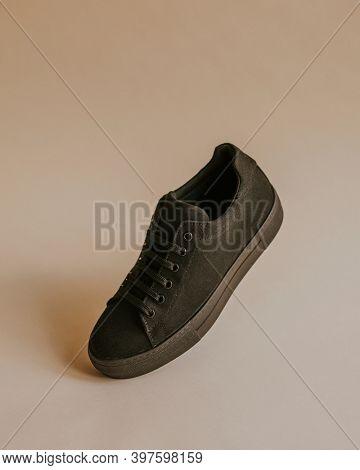 Black canvas sneaker shoe on beige