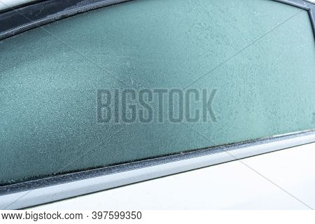 Frozen Glass Of The Car. The Patterns On The Side Car Glass. Winter Texture Background. Frozen Windo
