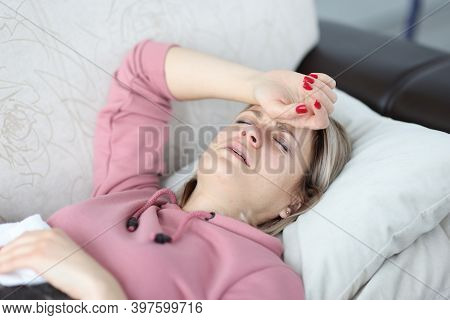 Tired Woman Lies On Sofa With Her Eyes Closed And Holds Her Hand On Her Forehead. Female Depression