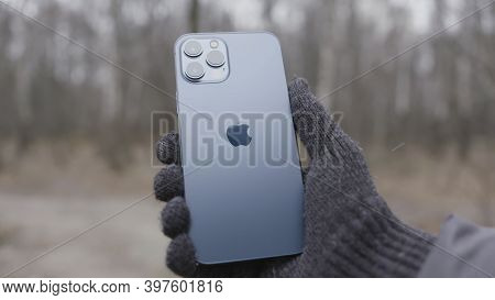 Moscow, Russia - 11.28.2020: Man Hand Holding Iphone Demonstrating Its Back Side. Action. New Apple