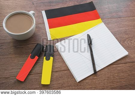 German National Flag, Pen, Notebook, Markers And A Cup Of Coffee On A Wooden Table, Foreign Language