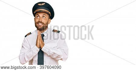 Handsome man with beard wearing airplane pilot uniform begging and praying with hands together with hope expression on face very emotional and worried. begging.