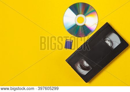 Video Cassette Videotape, Compact Disc, Flash Sd Card On A Yellow Background. Flat Lay Concept.