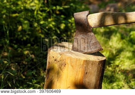 An Iron Ax With A Wooden Handle Stuck Into A Tree Stump. Ax And A Wooden Stump.