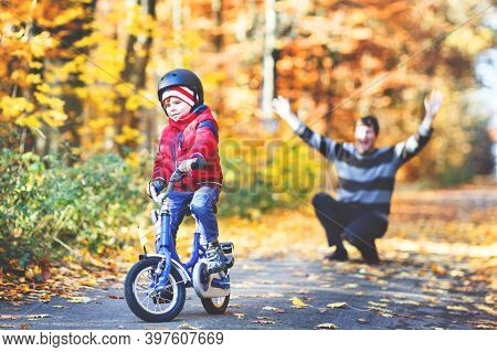 Little Kid Boy Learning Moving On Bicycle. His Father Teaching His Son Biking. Happy Man And Child.