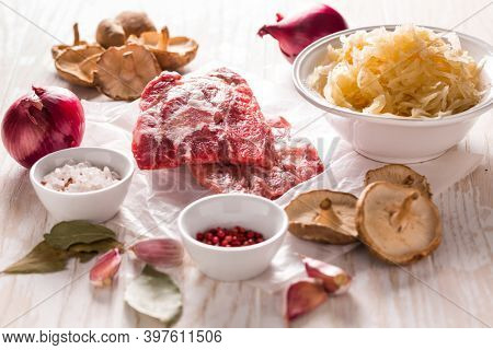Ingredients for hearty sour cabbage soup (sauerkraut soup) with meat, onion, garlic and spices on wooden table