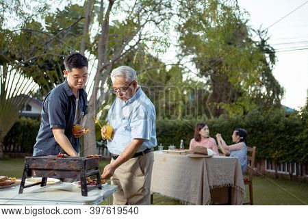 Happy Asian Family Dining And Tasting Juice On Glasses In Barbecue Dinner Party, Multi Generation Fa