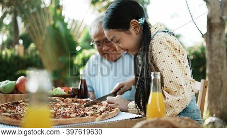 Happy Asian Grandchild Take A Bite Pizza, Multi Generation Family Enjoying Meal With Grandpa. They H