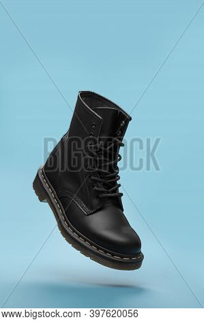Black Boots In The Air On The Blue Background . Fashion Shoes Still Life. Classic Unisex Black Lace-
