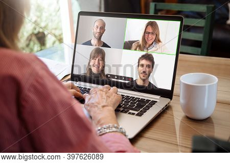 View Over Shoulder Of Senior Woman Talking By Video Call With A Group Of Young. Laptop Screen With S