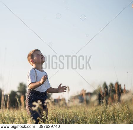 Boy Blowing Soap Bubbles While An Excited Kid Enjoys The Bubbles. Happy Teenage