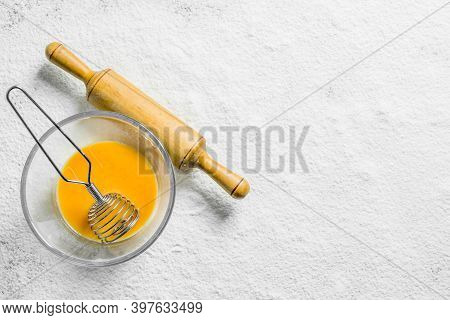 Beaten Egg In A Bowl With A Whisk And A Rolling Pin. On A White Background Of Flour