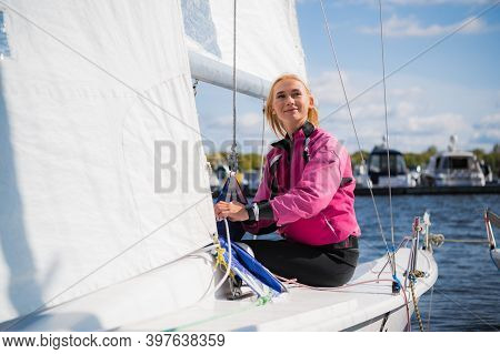 A Young Female Sailing Athlete Sets A Genaker Sail On Her White Sports Yacht To Go To A Regatta