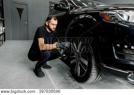 Side View Of Handsome Caucasian Male Car Wash Worker Holding In Hand Special Chemical Cleansing Solu